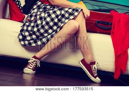 Packing problems necessary things during the trip concept. Woman sitting on sofa getting ready for vacation choosing clothes to pack into suitcase