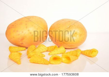 Fresh potatoes and chips on white background