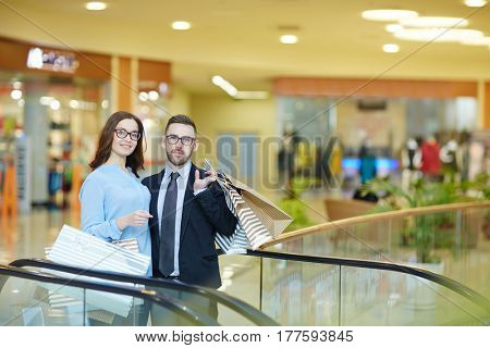 Young couple in eyeglasses standing by escalator in the mall