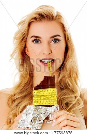 Young woman holding chocolate and eating measure tape