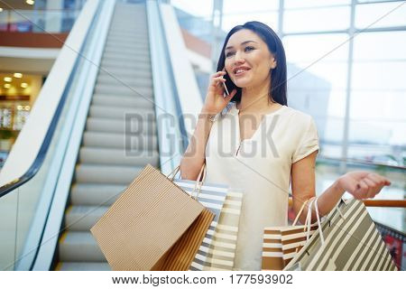 Happy modern girl speaking on smartphone after shopping
