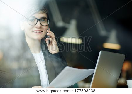 Waist-up portrait of smiling young manager sitting in cozy coffeehouse and calling to her colleague, view through cafe window