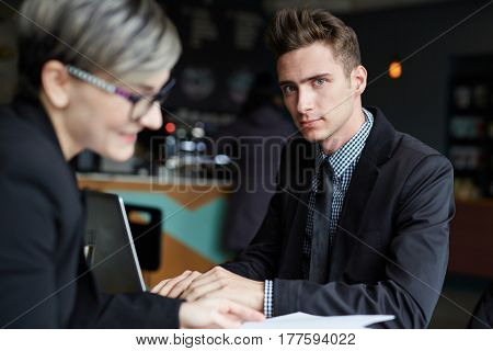Portrait of confident handsome businessman looking at camera while working on modern laptop, his pretty female colleague sitting opposite him in cafe and holding documents in hands