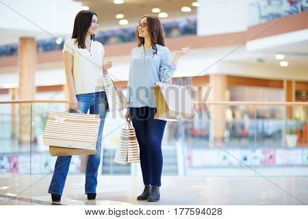 Smiling women discussing their shopping in the mall