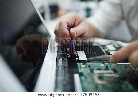 Closeup shot of male hands repairing parts in laptop using screwdriver and different tools on table in workshop