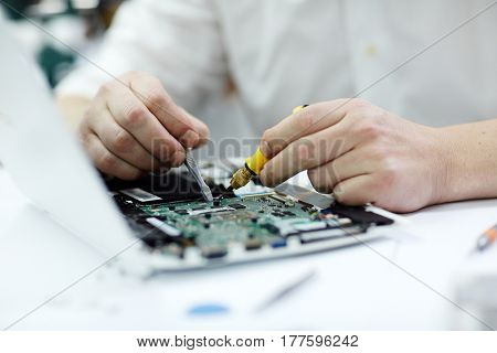 Closeup shot of male hands  working on disassembled laptop with screwdriver and tweezers looking for broken pats