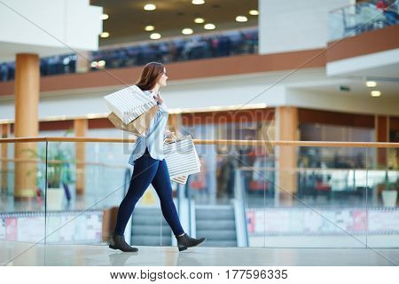Happy consumer with paperbags in hands walking down mall