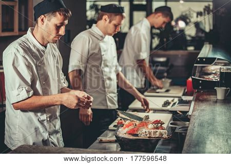 Three young white chefs dressed in white uniform decorate ready dish in restaurant. They are working on maki rolls. Preparing traditional japanese sushi set in interior of modern professional kitchen