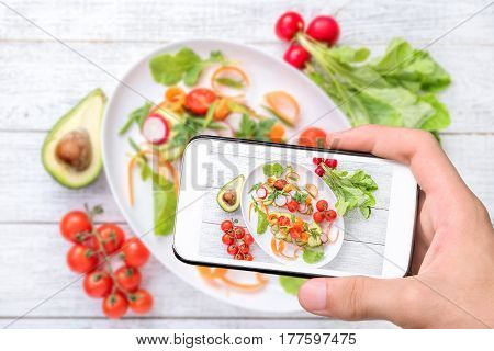 Hands taking photo vegan sandwich with avocado salad with smartphone.