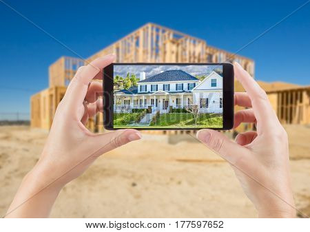 Female Hands Holding Smart Phone Displaying Photo of House with Unfinished Home Construction Behind.