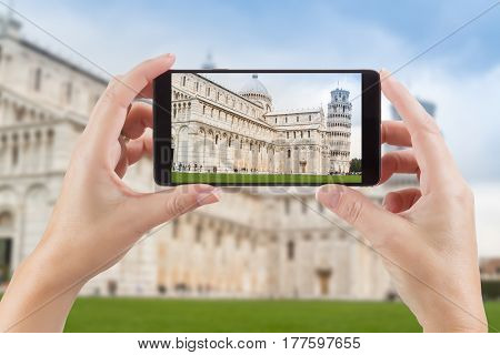 Female Hands Holding Smart Phone Displaying Photo of The Leaning Tower of Pisa Behind.