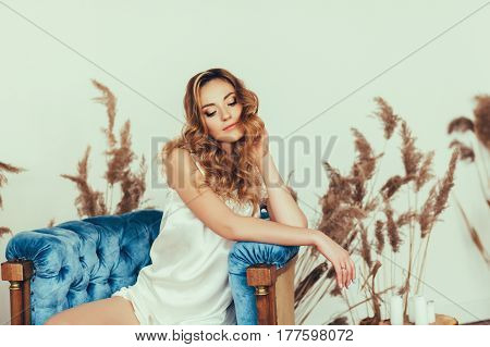 Gentle portrait of the bride in lingerie sitting on a chair