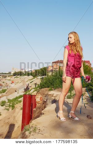 Portrait of young woman in pink costume with bouquet over city background