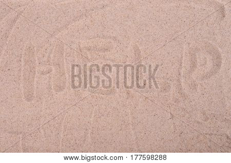 The inscription on the sand Help, close-up