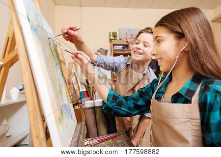 Creating positive atmosphere. Upbeat active playful kids standing in the studio and having painting lesson while expressing joy and painting