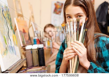 Enjoying free time together. Playful smiling happy kids sitting in the art studio and having painting class while expressing joy and holding paintbrushes