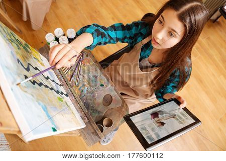 Using gadgets in the art process. Positive involved talented girl sitting in school and having art class while painting and holding tablet
