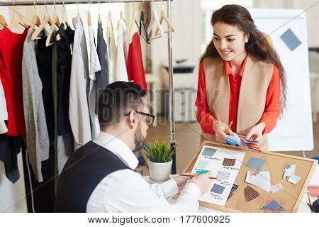 Fashion designers consulting while discussing trendy colors and fabrics
