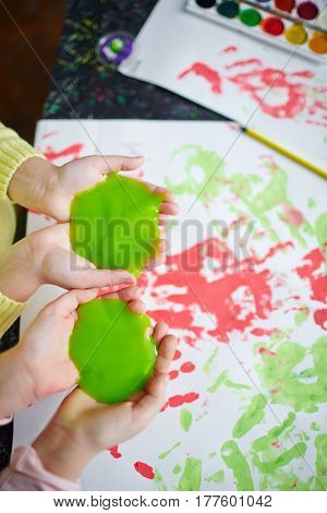 Girls holding green slime on their palms