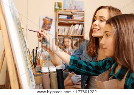 Enjoying my job. Delighted charming young woman sitting in the studio and having painting class while teaching children and expressing care and joy