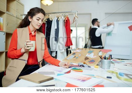 Young woman working over sketches of new fashion trends
