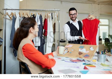 Two fashion designers discussing color and model of new stylish dress