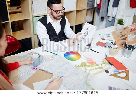 Confident man pointing at fashion sketch on paper while interacting with colleague