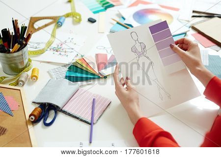 Dressmaker choosing trendy violet color for new collection of clothes