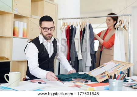 Creative fashion designer and his colleague working in studio