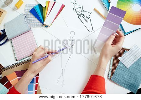 Fashion designer sketching new creative clothes