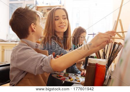 Enjoyable cooperation with children. Involved smiling beautiful teacher sitting in the art studio and conducting class while teaching children and expressing happiness
