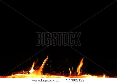 Fire and cinder isolated on black background. Fragment of fireplace in black.