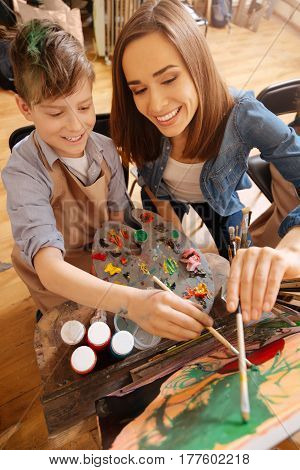Open new horizons together. Skilled careful experienced painter sitting in the art studio and conducting class while teaching children painting
