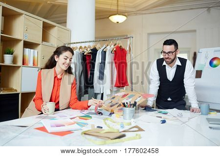 Happy designer choosing fabric samples for new collection of clothes