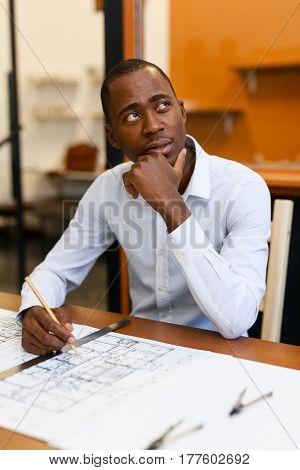 Pensive engineer looking aside while thinking over new idea