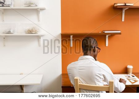 Modern young architect sitting by workplace and sksetching