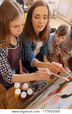 Repeat after me. Involved attractive young artist sitting in the studio and conducting art class while teaching children painting