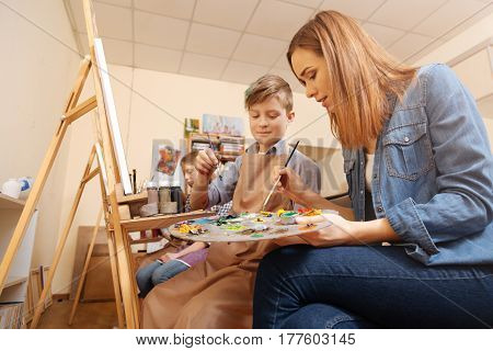 Painting together. Smiling happy young artist sitting in the studio and conducting art class while teaching child painting