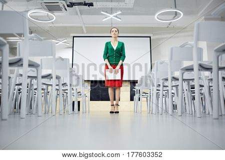 Strict teacher with notepad standing in the center of lecture-room