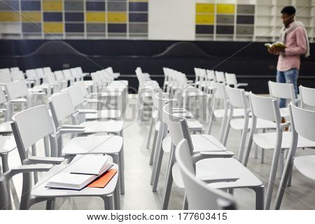 Rows of white plastic chairs and student preparing for exama on background