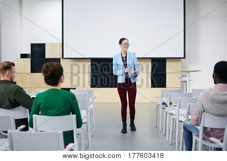 Happy young teacher talking to her students in conference-hall