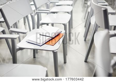 Open notebook and pen on chair in empty conference-hall