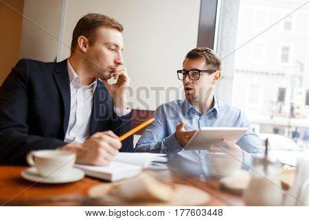 Businessmen analyzing sales at meeting