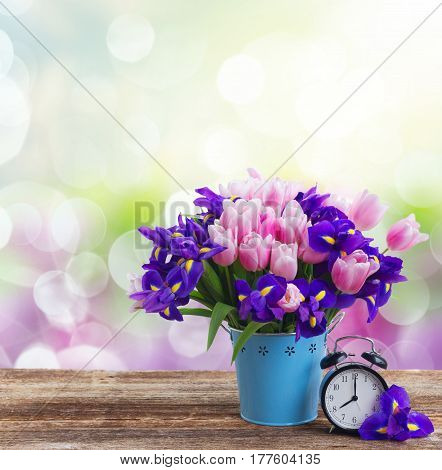 Spring time concept - retro alarm clock with bouquet of flowers over bokeh background
