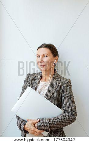 Senior lawyer with earphones holding laptop