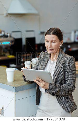 Modern businesswoman wit hearphones browsing in the net