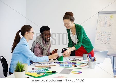 Young designer showing curious photo to co-workers during discussion