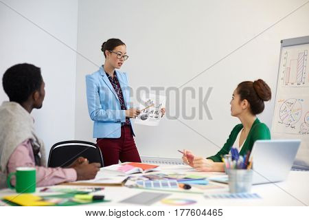 Young woman pointing at financial chart on paper while explaining data to colleagues