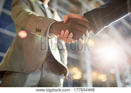 Low angle closeup shot of two business partners in handshake: unrecognizable African -American businessman shaking hands with Caucasian colleague in hall of modern glass office building at night time