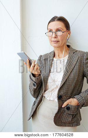 Elegant mature female with earphones listening to music
